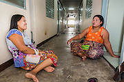 30 APRIL 2013 - MAHACHAI, SAMUT SAKHON, THAILAND:  Burmese women relax in the hallway of their apartment building in the Thai fishing port of Mahachai. The Thai fishing industry is heavily reliant on Burmese and Cambodian migrants. Burmese migrants crew many of the fishing boats that sail out of Samut Sakhon and staff many of the fish processing plants in Samut Sakhon, about 45 miles south of Bangkok. Migrants pay as much $700 (US) each to be smuggled from the Burmese border to Samut Sakhon for jobs that pay less than $5.00 (US) per day. There have also been reports that some Burmese workers are abused and held in slavery like conditions in the Thai fishing industry.          PHOTO BY JACK KURTZ