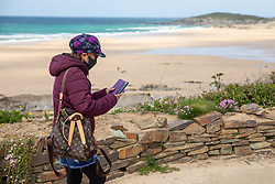 """© Licensed to London News Pictures. 11/05/2020. Newquay, UK. A woman wearing a mask walks past Fistral beach on the North coast of Cornwall, the day after British Prime Minister Boris Johnson announced a 'road map' to lift lockdown restrictions due to Covid-19, (Coronavirus). A rise in """"staycations"""" - the concept of holidaying in your home country rather than travelling abroad - is expected, with many visitors planning to visit Cornwall. However, an ongoing campaign titled """"#ComeBackLater"""" is trying to persuade tourists not to visit the county until it is safe to do so. Photo credit : Tom Nicholson/LNP"""
