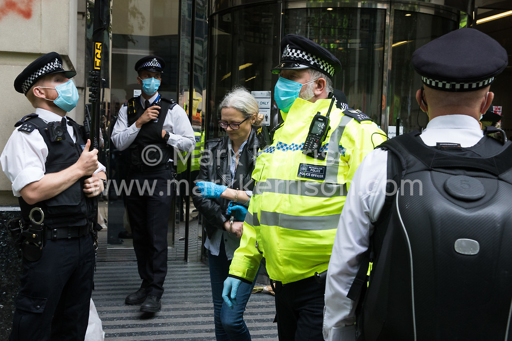 London, UK. 4th September, 2020. Metropolitan Police officers arrest an activist from HS2 Rebellion, an umbrella campaign group comprising longstanding campaigners against the HS2 high-speed rail link as well as Extinction Rebellion activists, who had glued herself to the doors of the Department for Transport during a protest. Activists glued themselves to the doors and pavement outside the building and sprayed fake blood around the entrance during a protest which coincided with an announcement by HS2 Ltd that construction of the controversial £106bn high-speed rail link will now commence.
