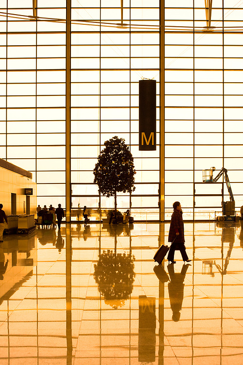 Pudong, Shanghai, Asia - A business woman with her suitcase in the Pudong international Airport of Shanghai.