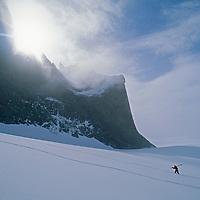 "A mountaineer hikes to ski new powder below Rakekniven Spire (""The Razor."")"