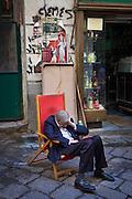 Morning Riposo. Shopkeeper in Piazza CaraccioloVicolo Mezzani, Palermo, Italy.