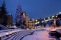 Evening view of Apart Hotel at Bukovel skiing resort, Ukraine. Hotel building decorated with Christmas lights. Skiing slope with lights on the background.<br /> <br /> Вечерний снимок отеля Apart Hotel в Буковели. Иллюстрация к удобному расположению возле лыжного подъемника.