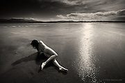 Nominee in Nude / B&W Spider Awards 2017<br /> <br /> There is always something special and deeply sensuous about touching wild water. The woman stretched her body and gently, slowly, rolled across the wet sand with no more than an inch of water beneath her slender body. Her long raven hair whipped in the warm West wind blowing down the estuary from the sea beyond the dunes. She revelled in the feelings; embraced by the elements; sinking her fingers into the saturated earth and pressing her flesh against the estuary, becoming a part of it, connected to it, supported by it. Droplets trickled over every inch of her body making the wind feel cool, goosebumps raised on her delicate skin, making her even more sensitive to the air around her. She was invigorated, purified.