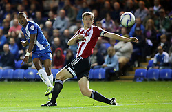 Peterborough United's Britt Assombalonga shoots at goal past Brentford's Tony Craig - Photo mandatory by-line: Joe Dent/JMP - Tel: Mobile: 07966 386802 08/10/2013 - SPORT - FOOTBALL - London Road Stadium - Peterborough - Peterborough United V Brentford - Johnstone's Paint Trophy