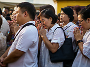 15 NOVEMBER 2018 - BANGKOK, THAILAND: People pray during the red cloth ceremony at Wat Saket, also called the Golden Mount. Wat Saket is on a man-made hill in the historic section of Bangkok. The temple has golden spire that is 260 feet high, which was the highest point in Bangkok for more than 100 years. The temple construction began in the 1800s during the reign of King Rama III and was completed in the reign of King Rama IV. A  red cloth (reminiscent of a monk's robe) is placed around the chedi at the top of  Golden Mount during the weeks leading up to the Thai holy day of Loy Krathong, which is November 22 this year.      PHOTO BY JACK KURTZ
