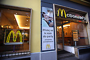 McDonald's fastfood franchise with signs in Czech along a street in the old section of the city.