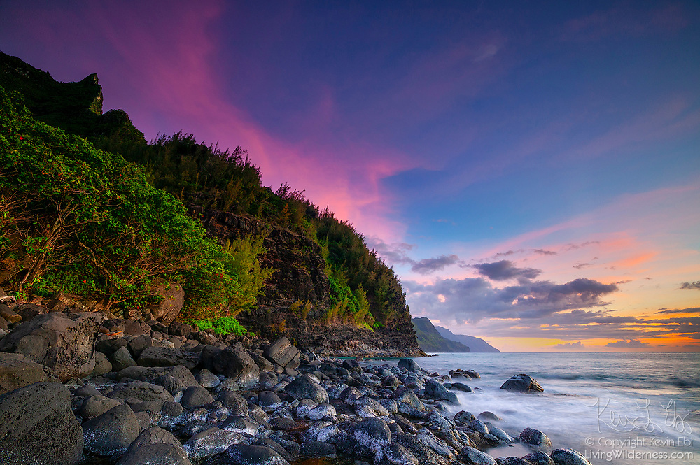A colorful, late-spring sunset colors the sky above the rugged cliffs of the Na Pali coast and the Pacific Ocean in this view from Ke'E Beach on Kauai's north coast.