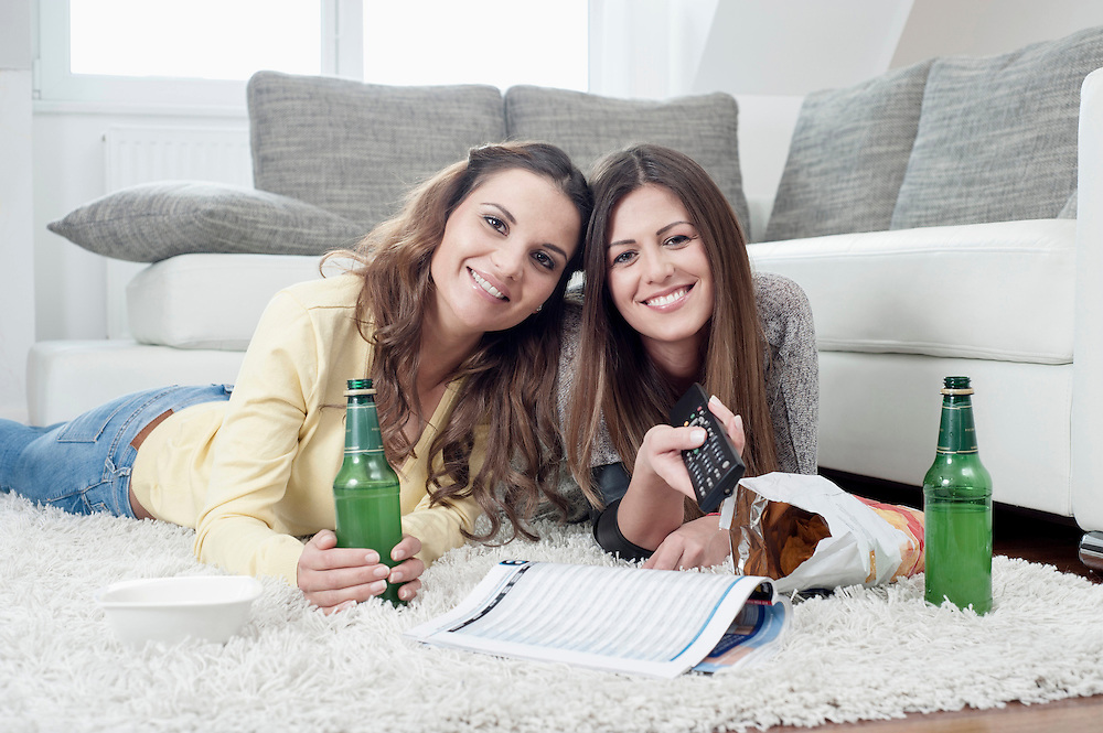 Two female friends lying side by side on carpet at home watching television