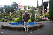 """Portmeirion, in North Wales, is a resort, where no one has ever lived. A self-taught Welsh architect named Sir Clough Williams-Ellis built it out of architectural salvage between the 1920s and 1970s, loosely based on his memories of trips to Portofino. Including a pagoda-shaped Chinoiserie gazebo, some Gothic obelisks, eucalyptus groves, a crenellated castle, a Mediterranean bell tower, a Jacobean town hall, and an Art Deco cylindrical watchtower. He kept improving Portmeirion until his death in 1978, age 94. It faces an estuary where at low tide one can walk across the sands and look out to sea. At high tide, the sea is lapping onto the shores. Every building in the village is either a shop, restaurant, hotel or self-catering accomodation. The village is booked out at high season, with numerous wedding receptions at the weekends. Very popular amongst the English and Welsh holidaymakers. Many who return to the same abode season after season. Hundreds of tourists visit every day, walking around the ornamental gardens, cobblestone paths, and shopping, eating ice-creams, or walking along the woodland and coastal paths, amongst a colourful assortment of hydrangea, rhododendrons, tree ferns and redwoods. The resort boasts two high class hotels, a la carte menus, a swimming pool, a lifesize concrete boat, topiary, pools and wishing wells. The creator describes the resort as """"a home for fallen buildings,"""" and its ragged skyline and playful narrow passageways which were meant to provide """"more fun for more people."""" It does just that.///A child wishing a wish in the wishing well. Ornamental central gardens of Portmeirion village. Flanked by Dome Gallery, Gothic tower, Renaissance collonades, with lwans, flowerbeds, topiary, pools and fountains."""