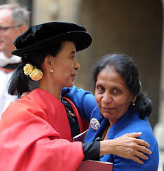 © Licensed to London News Pictures. 20/06/2012. Oxford, UK Aung San Suu Kyi (L) is hugged as she leaves Oxford University today 20 June 2012 after receiving an Honary Degree at the Encaenia Ceremony.  The Burmese democracy leader is to receive an honorary doctorate in civil law at annual ceremony honouring the brightest and best. Other honorees include: former MI5 Director General Baroness Manningham-Buller; author David John Moore Cornwell (aka John le Carre); Harvard University president Professor Drew Gilpin Faust; and Sony chief executive Sir Howard Stringer. Photo credit : Stephen Simpson/LNP