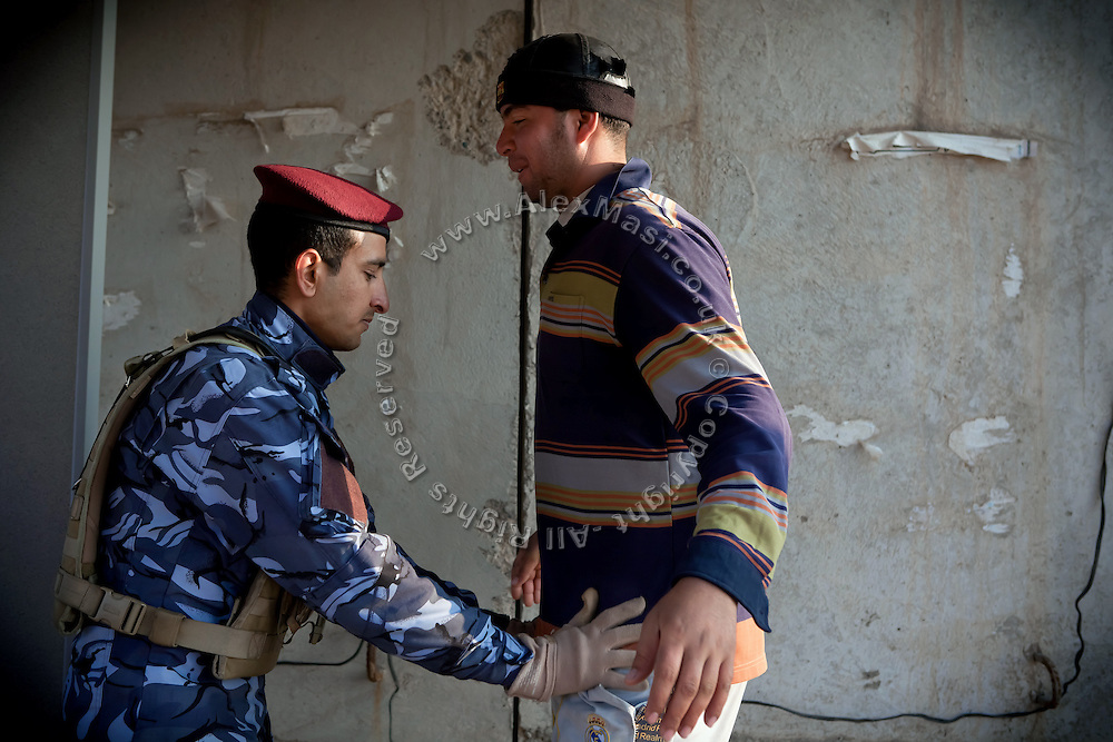 A member of the Iraqi Police is inspecting people walking through the main checkpoint to the city of Fallujah, Iraq, on the Highway N.10. (Baghdad-Fallujah-Ramadi)