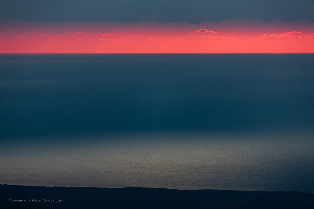 Nominated in 10th (2017) International Colour Awards (Nature category)<br /><br />Deep sunset though stormy weather cloud conditions over the Irish Sea, seen from the slopes of Mynydd Mawr mountain in Snowdonia