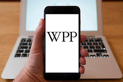 Using iPhone smartphone to display logo of WPP , British multinational advertising and public relations company
