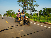 14 JULY 2015 - THAILAND: A tractor carrying farm workers on a damaged road in Pathum Thani province. The road bed collapsed because of subsidence. The drought that has crippled agriculture in central Thailand is now impacting residential areas near Bangkok. The Thai government is reporting that more than 250,000 homes in the provinces surrounding Bangkok have had their domestic water cut because the canals that supply water to local treatment plants were too low to feed the plants. Local government agencies and the Thai army are trucking water to impacted communities and homes. Roads in the area have started collapsing because of subsidence caused by the retreating waters. Central Thailand is contending with drought. By one estimate, about 80 percent of Thailand's agricultural land is in drought like conditions and farmers have been told to stop planting new acreage of rice, the area's principal cash crop.       PHOTO BY JACK KURTZ
