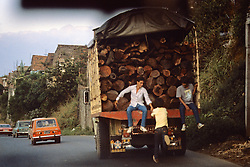 Truck Filled With Wood And People Hitching Ride