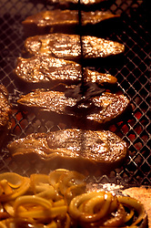 Stock photo of big steaks and onions grilling on an open outdoor grill