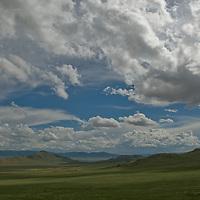 Summer cumulus clouds float above a remote valley near Muren, Mongolia.