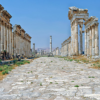 Apamea. Syria. View of the votive column and beautiful Prestige facade crowned by a triangular pediment from the majestic Colonnaded Street of the ancient city of Apamea.  The grand colonnaded avenue or cardo maxims is lined with tall columns with Corinthian capitals is one of the longest and widest in the ancient world and runs nearly two kilometres long.