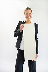 Portrait of businesswoman in black suit holding blank placard, smiling
