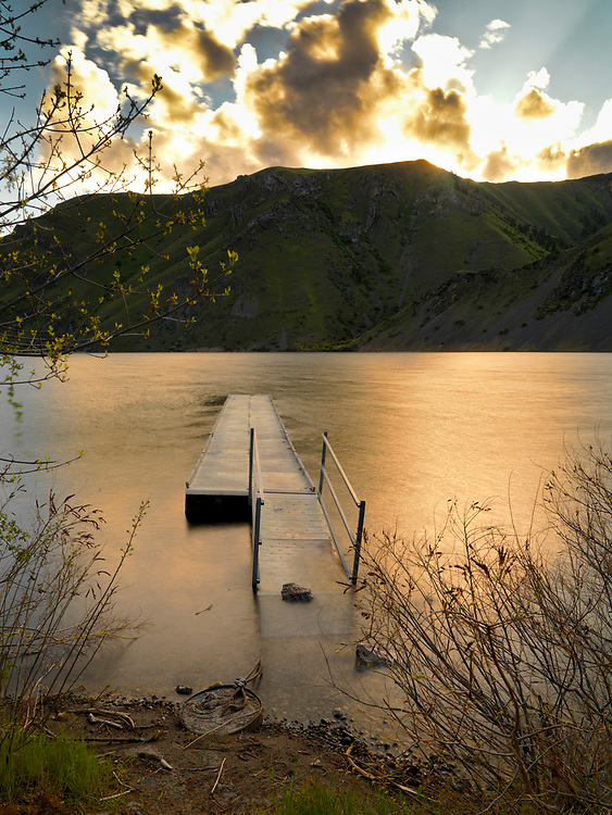 Floating dock in Hells Canyon holds on against current of the Snake River with a golden sunset.<br /> Licensing and Open Edition Prints