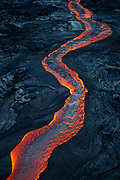 A 1/2 mile long river of lava flows swiftly and silently from a new breakout at Pu'u 'O'o, a vent on Kilauea's east rift zone. The stark contrast between the black of the surrounding crust, and oranges and reds of the river is so visually captivating...totally mesmerizing to witness in person.
