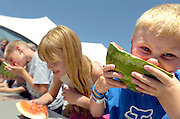NEWS&GUIDE PHOTO / PRICE CHAMBERS.Trenton Ross, 7, right gnashes teeth into a watermellon at the eating contest at the county fair on Friday. Ashley Potzernitz, 9, center, won the competition in the 7-9 age group.