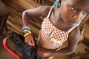 A girl closes the backpack with school materials she just received. <br /> Save the Children distributed education kits to students at Groupe Scolaire Quartier Lycée in Man, western Côte d'Ivoire. Children received a backpack with school supplies such as pens, pencils, sharpeners, notebooks, rulers, a pair of compasses and a portable chalkboard.