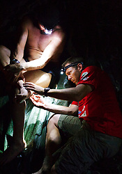 """© Licensed to London News Pictures. 11/10/2013. BRAZIL. Medic treating athletes foot with an injection late into the night after a gruelling day. With no lights in the camp they can only use head lights. Competitors take part in the Jungle Marathon 2013, the """"The toughest ultra marathon in the world"""" The race is 245 km long through the biggest jungle in the world, The Amazon. It attracts competitors from all countries world wide. Competitors run through territories of indigenous tribes throughout the 7 day race, where they stay with them as guests.. Photo credit : Alexander Beer/LNP"""
