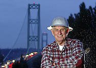 Bill Metheny, 86, wears his old hard hat and holds a spud wrench he used while helping build the bridge seen in the background. Client: The News Tribune
