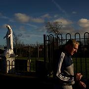 DUBLIN, IRELAND - DECEMBER 22, 2015: A man walks by a statue of the Virgin Mary in Sandyford, Dublin. CREDIT: Paulo Nunes dos Santos for The New York Times