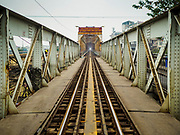 23 DECEMBER 2017 - HANOI, VIETNAM: The railroad track on the Long Bien Bridge. Long Biên Bridge is a historic cantilever bridge across the Red River that connects two districts, Hoan Kiem and Long Bien of the city of Hanoi, Vietnam. It was originally called Paul Doumer Bridge. The bridge was built in 1899-1902 by the architects Daydé & Pillé of Paris, and opened in 1903. Before North Vietnam's independence in 1954, it was called Paul-Doumer Bridge, named after Paul Doumer - The Governor-General of French Indochina and then French president. At 1.68 kilometres (1.04 mi) in length, it was, at that time, one of the longest bridges in Asia. For the French colonial government, the construction was of strategic importance in securing control of northern Vietnam. From 1899 to 1902, more than 3,000 Vietnamese took part in the construction.    PHOTO BY JACK KURTZ