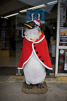 A penguin statue is dressed up like Santa Claus outside of a store in Ushuaia, Argentina.