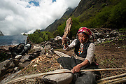 Tshring Tamang wearing traditional Tibetan dress splits bamboo, in the Langtang Valley, Nepal, 27th May 2009. <br /> <br /> According to Dorothea Stumm, a glaciologist at the Nepal-based International Centre for Integrated Mountain Development, a massive hanging glacier cracked when an earthquake struck at 11.56am on the 25th April 2015. The ice formed a cloud that gathered snow and rocks and then funnelled down the mountain, burying Langtang village, and creating an enormous pressurised blast. 400 residents of the village and up to 100 trekkers are believed to have been killed.<br /> <br /> PHOTOGRAPH BY AND COPYRIGHT OF SIMON DE TREY-WHITE<br /> <br /> + 91 98103 99809<br /> email: simon@simondetreywhite.com<br /> photographer in delhi