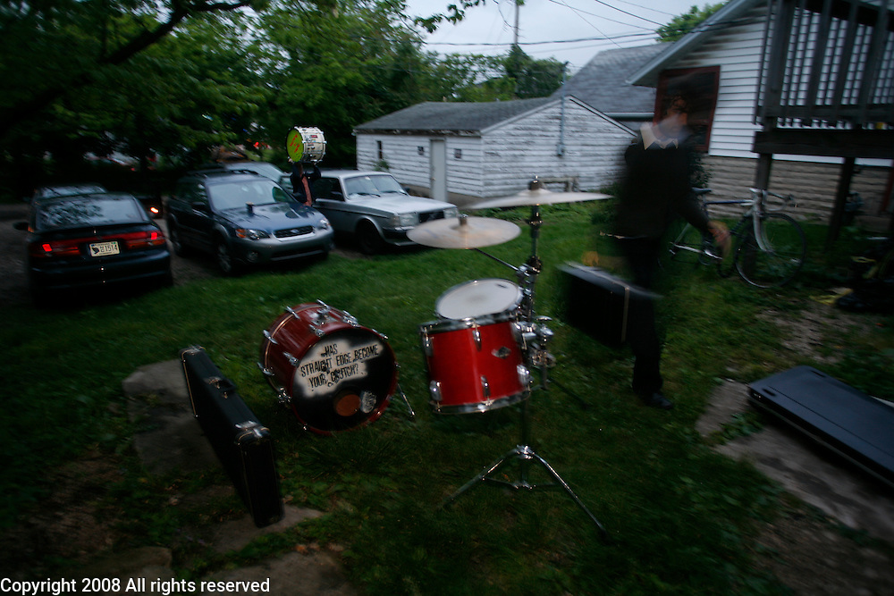 """Zak carries instruments to a basement show at """"Eye of the Tiger"""" house on Washington Street in Bloomington."""