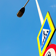Low angle view of street light with warning sign