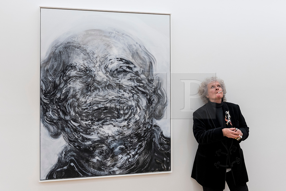 """© Licensed to London News Pictures. 14/10/2020. LONDON, UK. Artist Maggi Hambling poses with her work """"Laughing"""", 2018, at the preview of Maggi Hambling: 2020 at Malborough Gallery in Mayfair.  The exhibition of recent paintings coincides with Hambling's 75th Birthday and runs 15 October to 21 November 2020.  Photo credit: Stephen Chung/LNP"""