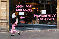 Edinburgh, Scotland, UK. 17 October 2020. Saturday afternoon in Edinburgh city centre during 16 day short circuit lockdown and bars are closed but cafes remain open. Streets in the Old town are very quiet and reminiscent of the eerie emptiness seen during the full lockdown earlier this year. Scran on Cockburn Street has put it's opinion of the lockdown on the windows.  Iain Masterton/Alamy Live News
