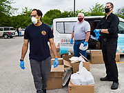 21 MAY 2020 - DES MOINES, IOWA: Volunteers wait for people at a drive through emergency food distribution in Evelyn K. Davis Park in central Des Moines. All of the 485 meals were distributed in about an hour. The economic fallout of the pandemic is being felt throughout Iowa. On May 21, 2020, Iowa reported that 187,375 people had filed for unemployment since the beginning of the COVID-19 pandemic and resulting economic shutdown. Emergency food pantry has also increased in that time, as many Iowans in low wage jobs used emergency food banks and pantries for the first time. The Food Bank of Iowa said Thursday that demand in April 2020 was 31% higher than demand in April 2019, mostly because of unemployment caused by the Coronavirus (SARS-CoV-2) pandemic. The emergency food distribution Thursday was organized by the city of Des Moines, Food Bank of Iowa, Central Iowa Shelter and Services, Urban Dreams and Orchestrate Hospitality.      PHOTO BY JACK KURTZ