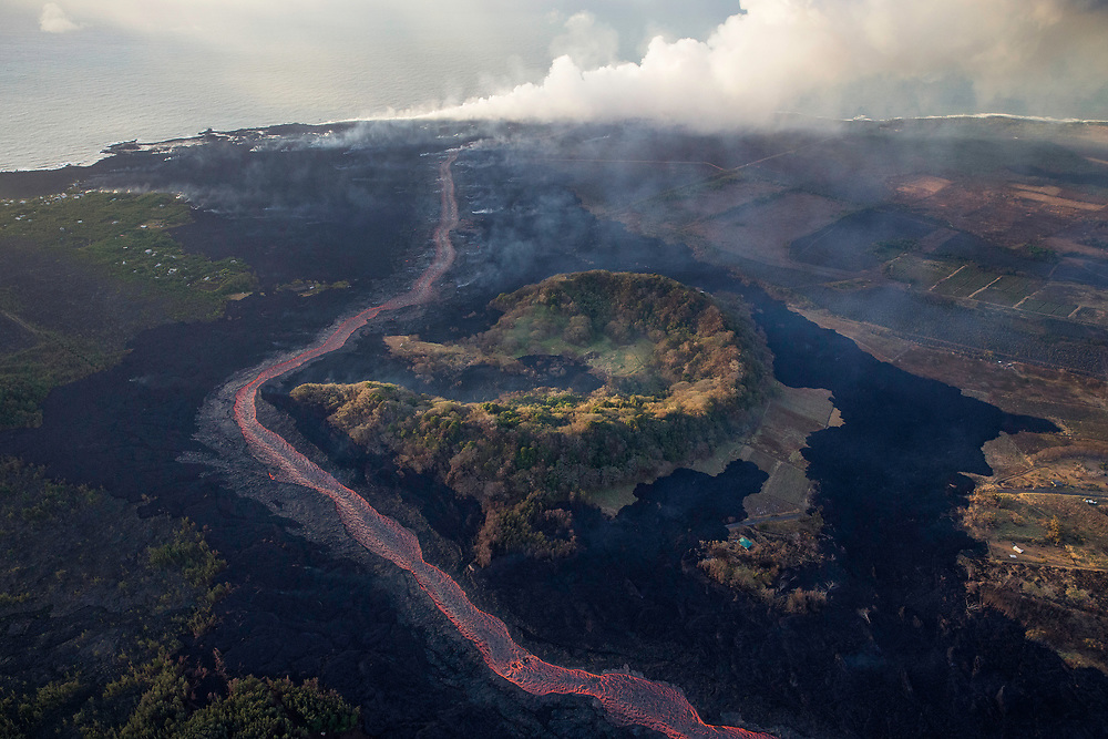 Kilauea's east rift zone: The early morning light kisses the lip of Kapoho crater, as the river of lava bends around it.