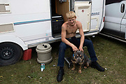 A tattooed man sits on the step of his camper van with his imported pocket pitbull dog, called Boss, in between his legs at Appleby Horse Fair, the biggest gathering of Gypsies and travellers in Europe, on 14th August, 2021 in Appleby, United Kingdom. Appleby Horse Fair attracts thousands from Gypsy, Romany, and traveller communities annually, making it the biggest gathering of its kind in Europe. Generally held for a week every June, the fair was postponed in 2020 and pushed forward to August in 2021 due to Coronavirus.