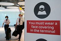 © Licensed to London News Pictures. 16/07/2021. London. British Airways air crew members wearing face coverings walk past a 'You must wear a face covering in the terminal' poster on display at Terminal 5 at London Heathrow Airport. The UK has reported 51,870 new COVID-19 cases in the latest 24-hour period- the highest number since 15 January, as Freedom Day approaches on 19 July. Photo credit: Dinendra Haria/LNP
