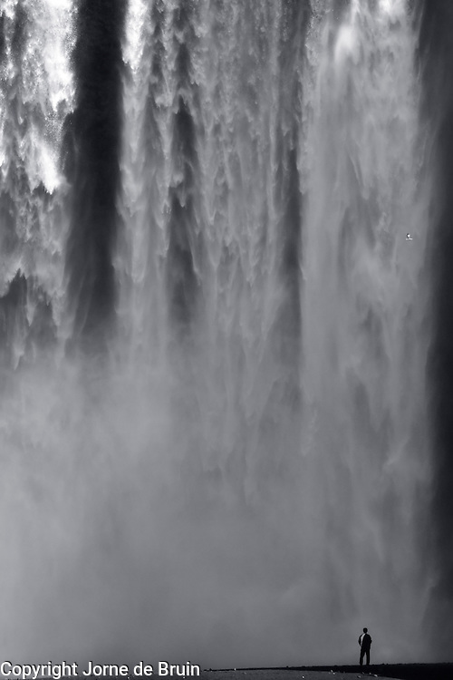 A Man is standing in front of the Skogafoss waterfall in southern iceland.