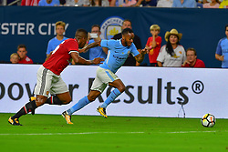 Manchester City midfielder Raheem Sterling (7) sprints to keep take control of the ball from Manchester United defender Antonio Valencia (25) during play a the International Champions Cup match between Manchester United and Manchester City at NRG Stadium in Houston, Texas