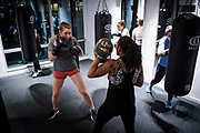 WASHINGTON, DC - NOVEMBER 14: Juliette Singarella (left) works out with coach Monica Jones, during a boxing conditioning class at NUBOXX on Wednesday, November 14, 2018 in Washington, DC. Once a sweaty, gritty environment of men, the recent trend of fitness boxing is now all about brightly-lit studios and fresh millennial faces working the heavy or speed bag. (Photo by Pete Marovich For The Washington Post)