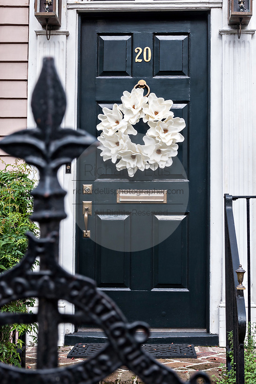 A white wreath on a black wooden door on a historic home decorated for Christmas on Tradd Street in Charleston, SC.