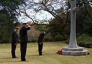 A official lays a wreath of poppies at a small Cross watch by a British naval officer and British Ambassador, Paul Madden (far left) during the  Remembrance Sunday ceremony at the Hodogaya, Commonwealth War Graves Cemetery in Hodogaya, Yokohama, Kanagawa, Japan. Sunday November 12th 2017. The Hodagaya Cemetery holds the remains of more than 1500 servicemen and women, from the Commonwealth but also from Holland and the United States, who died as prisoners of war or during the Allied occupation of Japan. Each year officials from the British and Commonwealth embassies, the British Legion and the British Chamber of Commerce honour the dead at a ceremony in this beautiful cemetery.
