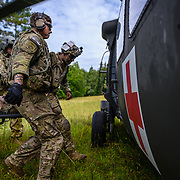 """U.S. Army Soldiers from 4th Battalion, 319th Airborne Field Artillery Regiment """"King"""" load a casualty into a waiting MEDEVAC helicopter during Saber Junction 20, Aug. 18, 2020, at Hohenfels Training Area. Saber Junction 20 is a 7th Army Training Command-conducted, U.S. Army Europe-directed annual exercise designed to assess the readiness of the U.S. Army's 173rd Airborne Brigade to execute unified land operations in a joint, combined environment, and to promote interoperability with participating allies and partner nations. This year's exercise will take place primarily at 7ATC's Grafenwoehr and Hohenfels Training Areas in Bavaria. U.S. military forces stationed in Europe routinely conduct these types of exercises with allied and partner nations to enhance interoperability and readiness. (U.S. Army photo by Sgt. 1st Class Garrick W. Morgenweck)"""