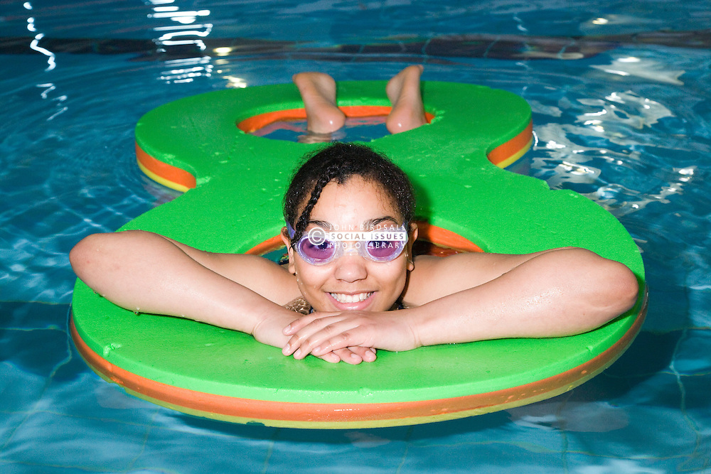 Girl playing with inflatable float in the swimming in the pool at her local leisure centre,