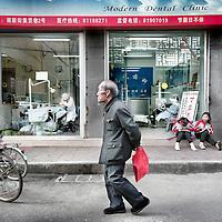 China,Xian ,maart 2008..Straattafereel met op de achtergrond een etalage van een tandartspraktijk Modern Dental clinic genaamd.Een oude man gekleed in een ouderwets Communistisch pak schuift door de straat.